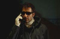 Clive Owen como o misterioso líder dos assaltantes